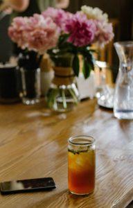 mason jar de thé glacé au puerh sur une table avec un vase de fleurs et un téléphone portable