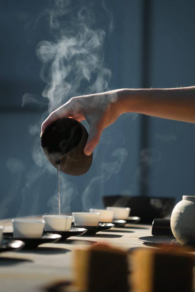 thé puerh dans des bols blancs, main qui sert de l'eau chaude dessus depuis un bol noir