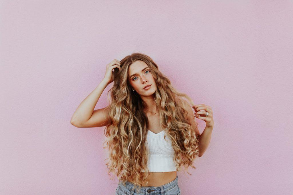 femme avec long cheveux bouclés blond miel sur fond rose pale